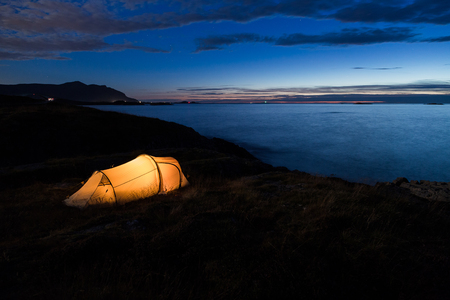 Iluminated tent in front of the Atlantic coast in Norway Stock Photo