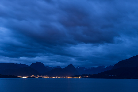 Iluminated city in front of a mountain range in Norway