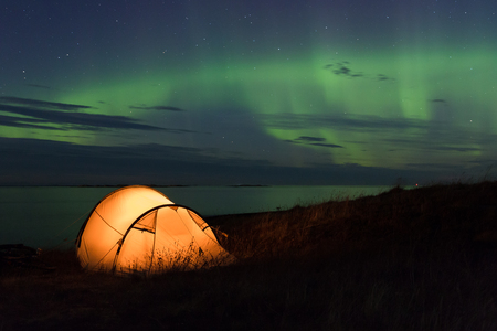 Northern lights dancing over an iluminated tent at the Atlantic coast in Norway Stock Photo