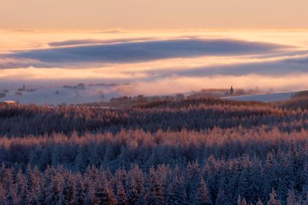 erzgebirge: winter landscape during the sunrise with fog
