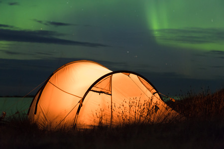Northern lights dancing over an iluminated tent at the Atlantic coast in Norway Stockfoto