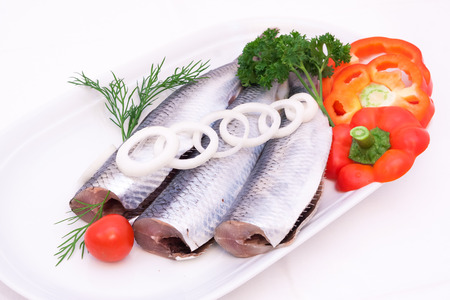 fresh herrings with a composition of green salad, tomatoes, onions and persley on wihte