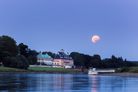 Partial lunar eclipse during moonrise over Pillnitz castle in Dresden, Germany