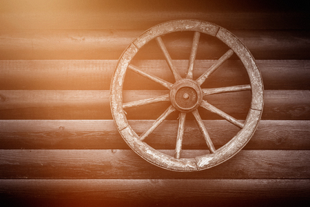 Old wooden cartwheel on the wall of a building