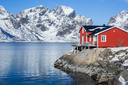 Red fisherman´s house on Lofoten islands in front of a fjord at a beautiful sunny winter day Editorial