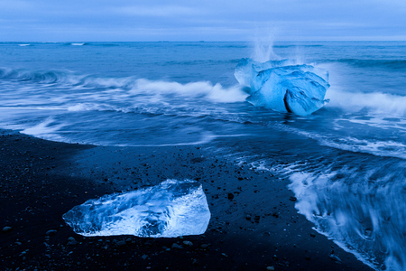 Ice floes lying on a black beach near Jokulsarlon glacier lagoon in Iceland