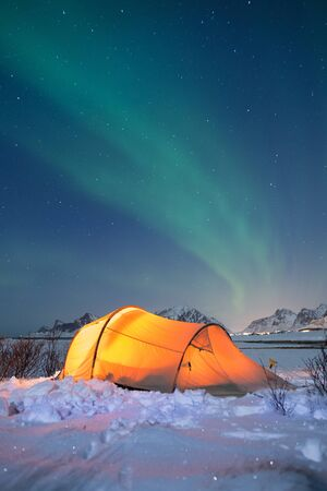 Illuminated tent under northern lights on Lofoten islands in winter