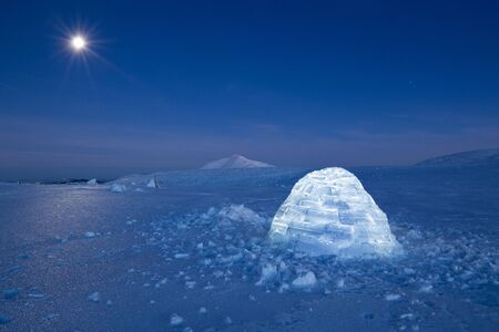 Iluminated igloo during a cold winter nights with bright moonshine Standard-Bild