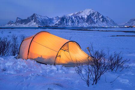 Illuminated tent at night on Lofoten islands in winter