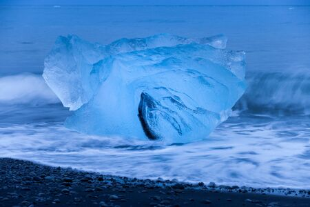 Ice floes lying on a black beach near Jokulsarlon glacier lagoon in Iceland