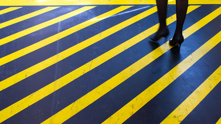 femal: young women steps over a yellow striped footpath in a industrial building