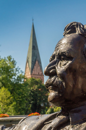 View of a sculpture of Mark Twain at a public place. Background the Nicolai Church. One of the most visit places at Luenburg Germany