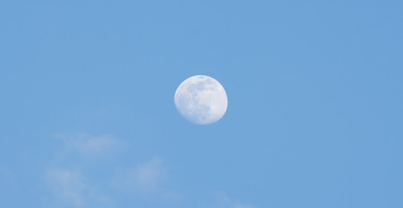 during: The full moon in the sky during the day. Stock Photo