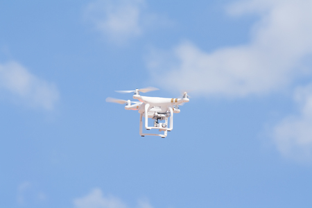 remote controls: Udon Thani, Thailand, August 16, 2015: White drone, quadrocopter, with photo camera flying in the blue sky. Concept. Aircraft, remote unmanned aircraft.