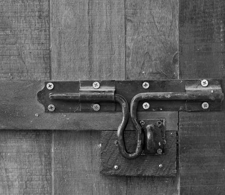 latch: Latch wooden door, black and white tones.
