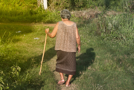 deteriorated: Old woman using a cane to support walking down the aisle Stock Photo