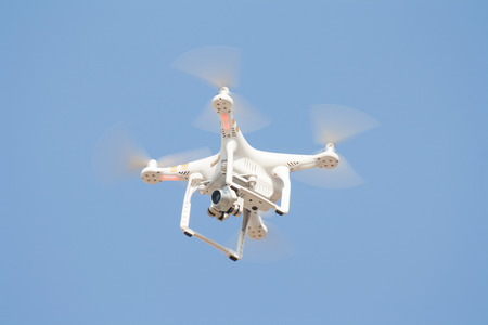 drones: UDON THANI, THAILAND, DECEMBER 11, 2015: Drones using aerial photography in the important event, White drone, quadrocopter, with photo camera flying in the blue sky.
