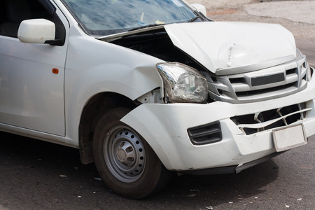 collisions: The front of the car damaged in an accident. Automobile White. Car accident on the road. Stock Photo