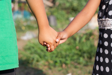 Children shaking hands in the meadow, light fair from the sun.