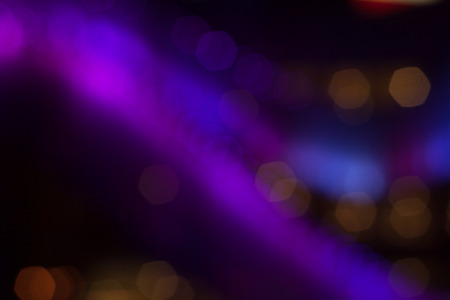Abstract background of out of focus lights at night. Bokeh shimmering light. Blurred multicolored lights in the darkness.