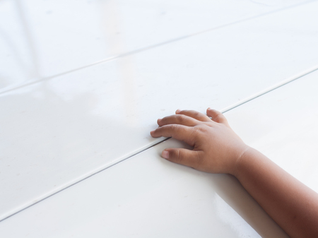 The boys hands are placed on a white platform. Space of text. Imagens