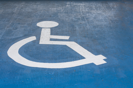 Parking lot symbol for the disabled on the concrete floor.