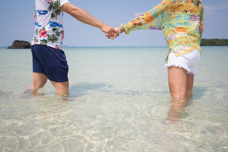 Couples holding hands to swim to the sea, shallow water.