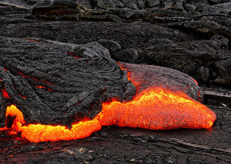 Hot magma escapes from an earth column as part of an active lava flow, the glowing lava slowly cools and freezes - Location: Hawaii, Big Island, volcano