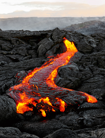 A lava flow emerges from an earth column in a black volcanic landscape, in the sky shows the first daylight - Location: Hawaii, Big Island, volcano Stock Photo