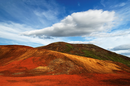 Colorful deposits of volcanic ash in reds and yellows against a green hill, above blue sky with a striking cloud formation. Stock Photo