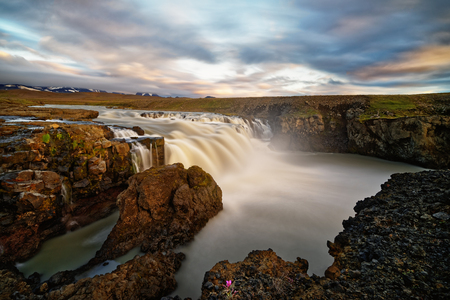 Wild waterfall in a wide landscape for sunset, water movement and cloud train are emphasized by long exposure - Location: Iceland, highlands