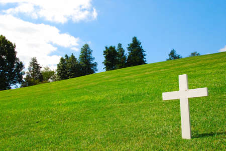 obelisk stone: White Cross on a grassy field on a beautiful sunny day