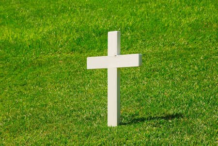 gravesite: White Cross with a green grassy background. Stock Photo
