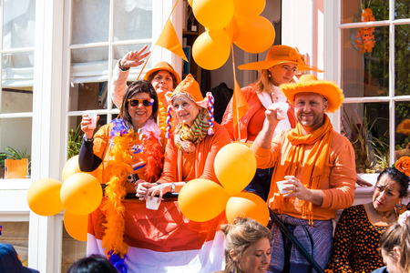 Amsterdam, Netherlands - April, 2018: People on the street celebrate Kings day in Amsterdam city, Netherlands
