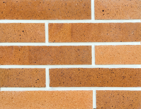 Tiles of house facade, red brick wall background.