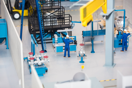 Scale model of industrial plant with worker working at the machine Stock Photo