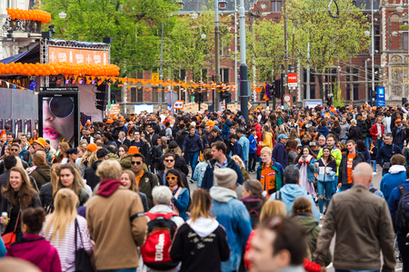 Amsterdam, Netherlands - April, 2018: Crowd of people on the street celebrate Kings day in Amsterdam city, Netherlands