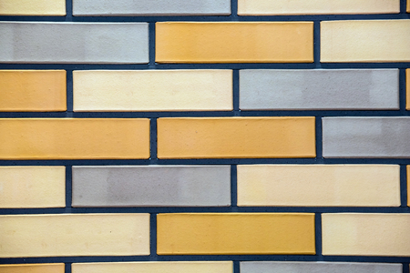 Tiles of house facade, blue, white and brown brick wall background. 免版税图像