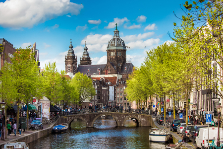 Amsterdam, Netherlands - April, 2018: St. Nicholas Basilica view. Spring day in Amsterdam with bridge, boats and bicycles
