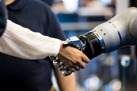 Roboterhand, die menschliche Hand schüttelt