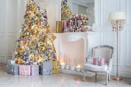 White room interior with New Year tree decorated, present boxes and fireplace