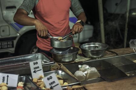 A man prepare steamboat for customer Imagens
