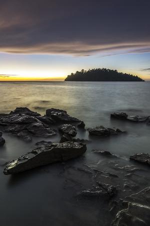 Nice seascape with rocky beach and an island a background