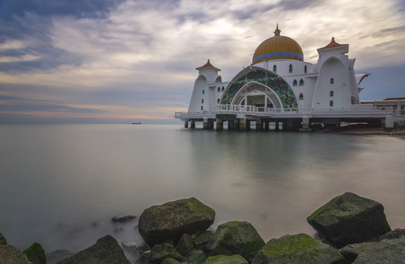Malacca straight mosque with alga covered rock Imagens