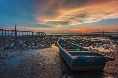 Fisherman boat stranded at the muddy beach side during burning sunset Imagens