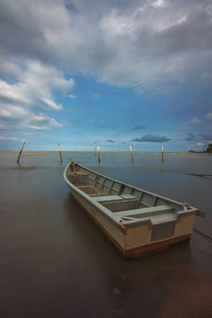 Lonely fisherman boat stranded at the beach shore Imagens