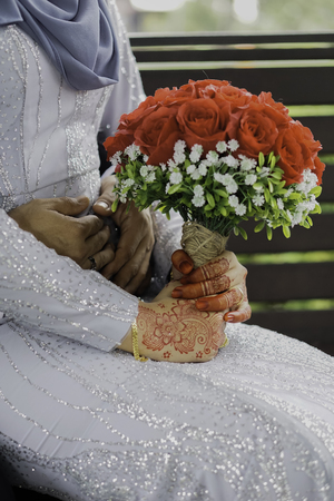 A couple malay wedding sit and holding a bouquet of flower Imagens