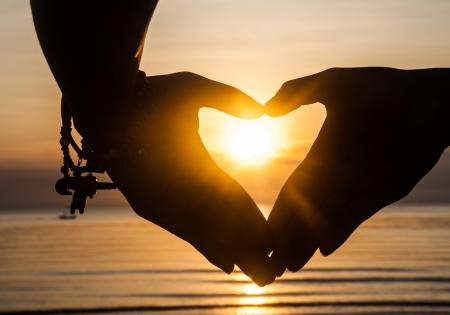 hand make heart with sun light