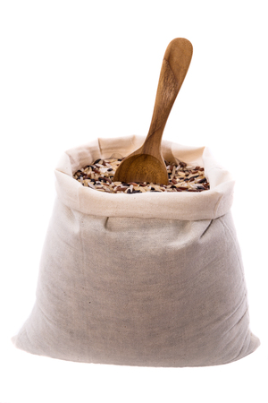 Rice in sack with wooden spoons