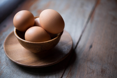Eggs in wooden bowl on wood backgrounds